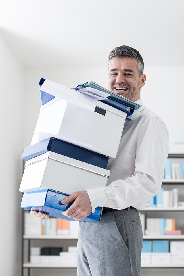Happy office worker carrying boxes