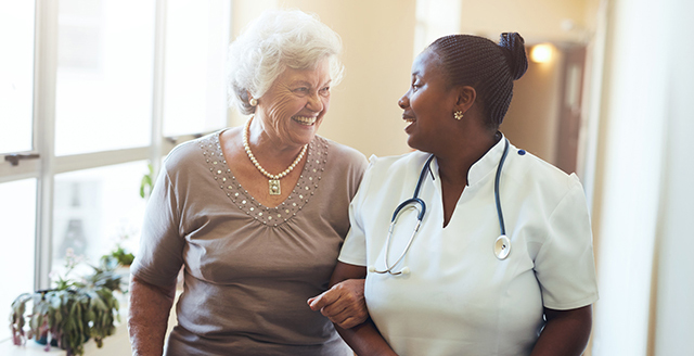 Nurse assisting senior woman at nursing home